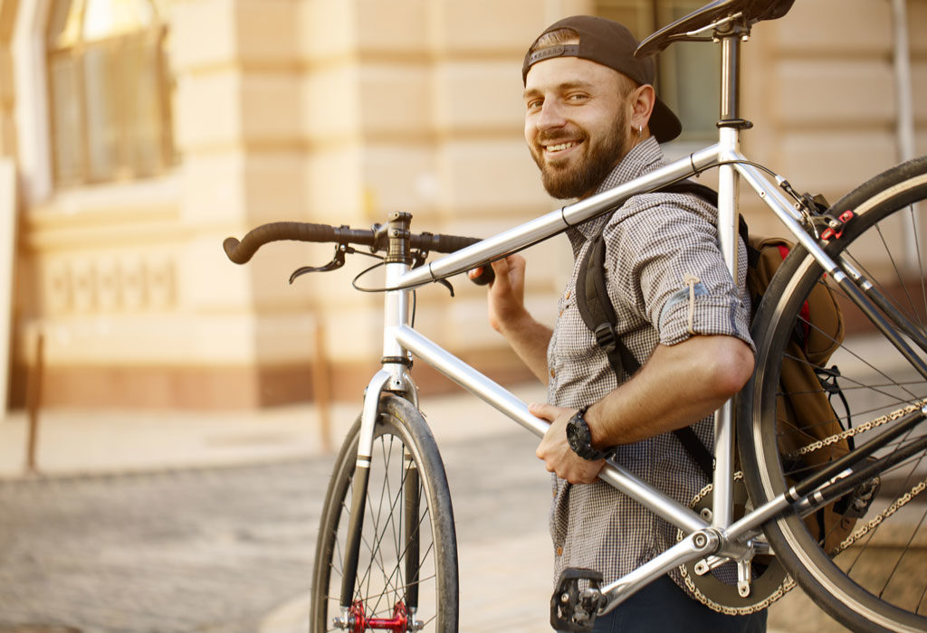 A man smiling while carrying a bicycle on his shoulder