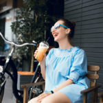 woman-sitting-on-bench-outside-with-bicycle-and-beverage